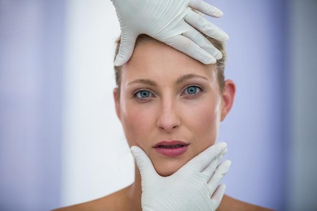 Doctor examinando pacientes femeninos cara de tratamiento cosmético