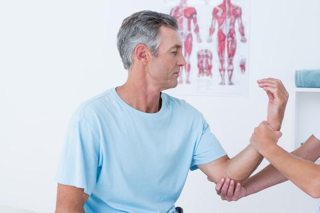 Doctor examinando su brazo paciente
