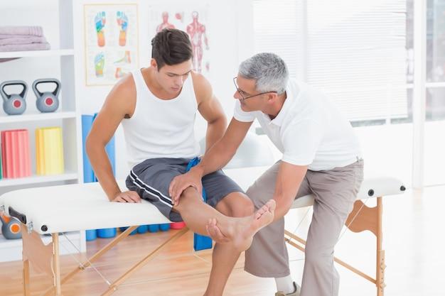 Doctor examinando su paciente rodilla