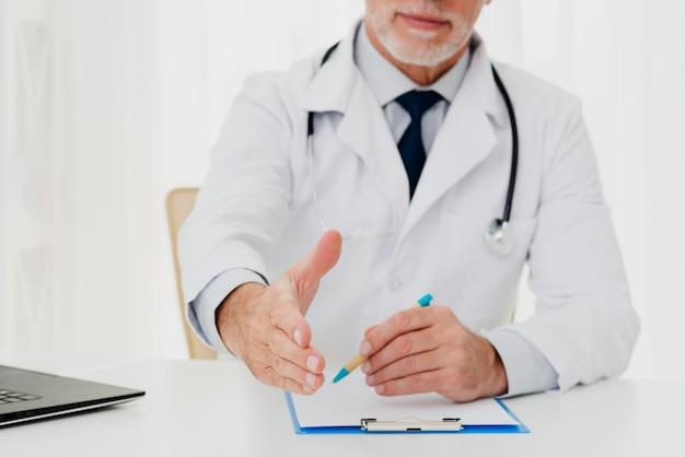 Doctor extendiendo su mano mientras está sentado