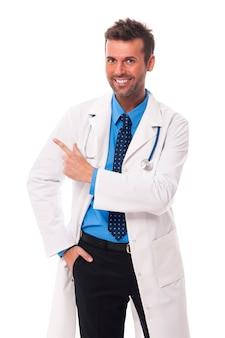 Doctor feliz apuntando al espacio de la copia