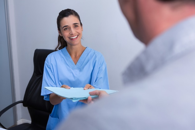 Doctor feliz dando archivo al paciente