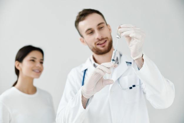 Doctor feliz sosteniendo una jeringa con la vacuna covid-19 y una paciente en el fondo