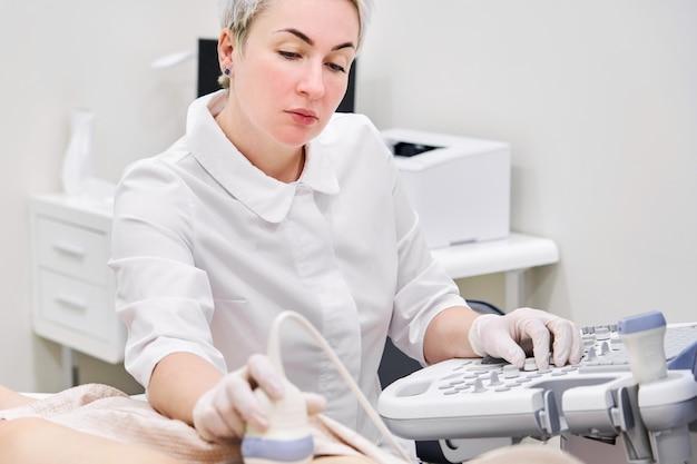 Doctor en funcionamiento escáner de ultrasonido para el diagnóstico del paciente
