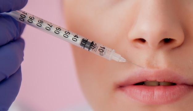 Doctor en guantes dando inyección de botox mujer en labios