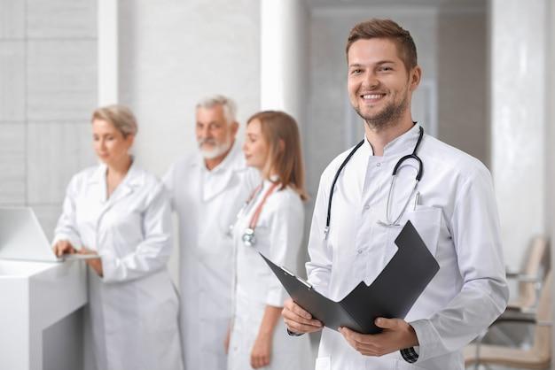 Doctor guapo posando, grupo de terapeutas de pie detrás.