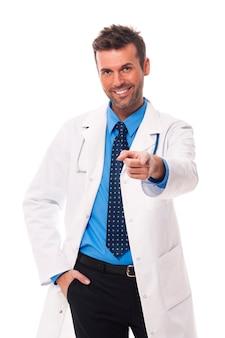 Doctor guapo y sonriente apuntando al lado de la cámara
