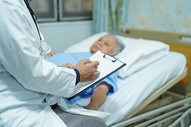 Doctor hablando de diagnóstico con mujer senior asiática.