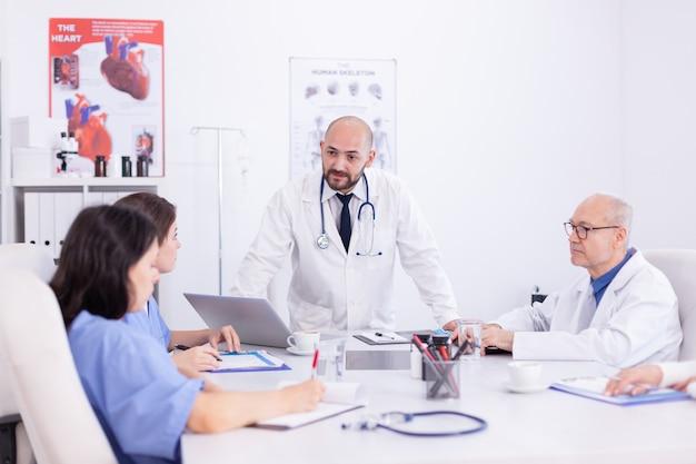 Doctor hablando de pie y hablando con el personal médico sobre el tratamiento del paciente. terapeuta experto de la clínica hablando con colegas sobre enfermedades, profesional de la medicina.