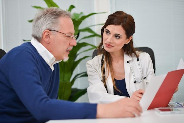 Doctor hablando con su paciente mientras muestra algunos documentos
