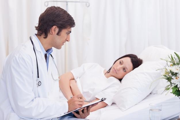 Doctor hablando con su paciente que acaba de despertar.