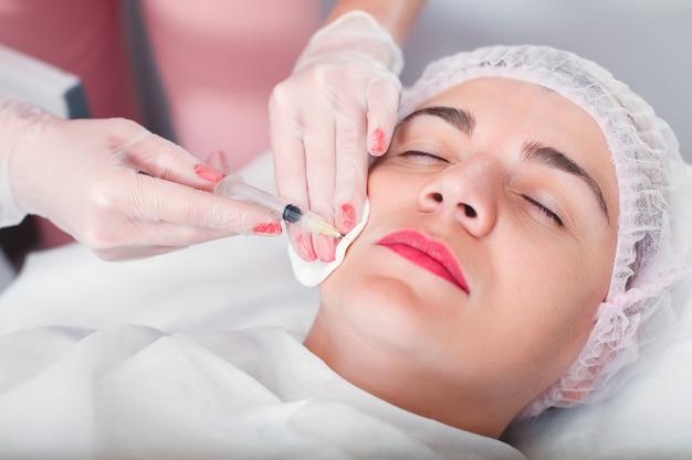 El doctor hace una jeringa de inyección en la cara de la mujer. tratamiento regenerador.