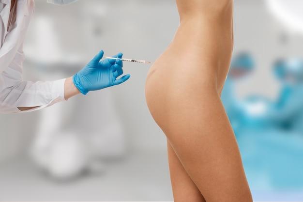 Doctor haciendo una inyección en el cuerpo.