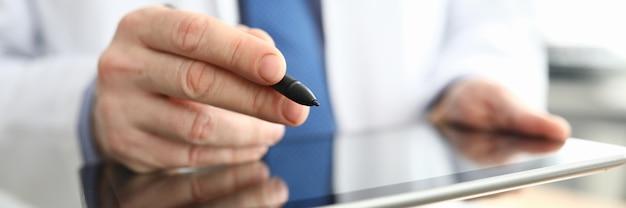 Doctor haciendo notas en la tableta gráfica de cerca