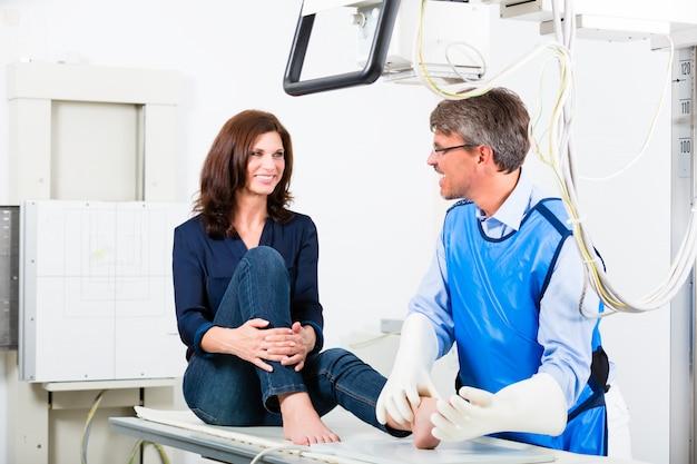 Doctor haciendo radiografía de pierna de paciente en cirugía.