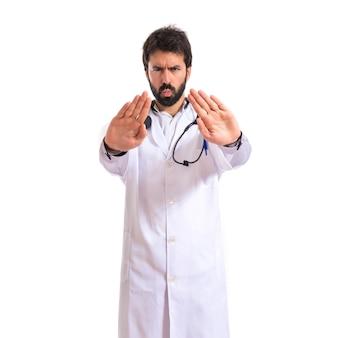 Doctor haciendo señal de stop sobre fondo blanco