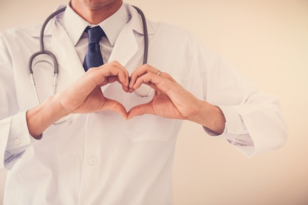 Doctor haciendo sus manos en forma de corazón, salud del corazón, concepto de seguro de salud