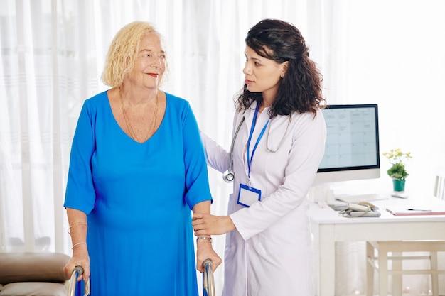 Doctor helpig mujer mayor