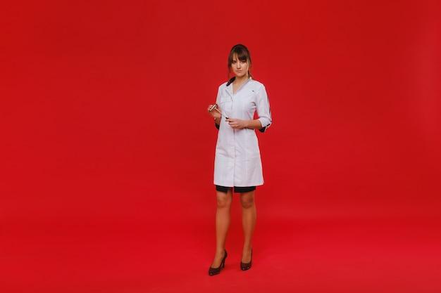 Doctor hermosa chica sostiene un martillo de reflejos y sonríe a la cámara aislada en rojo.