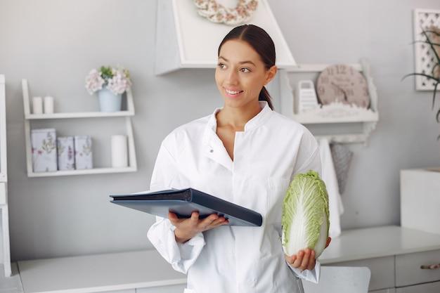 Doctor hermoso en una cocina con verduras