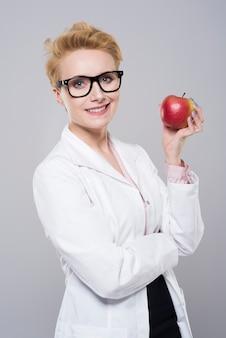 Doctor hermoso joven que sostiene la manzana madura