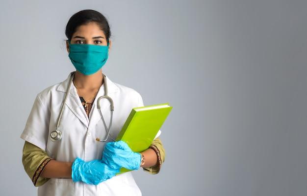 Doctor hermoso de la mujer joven que presenta con informe médico o libro y que muestra la muestra.