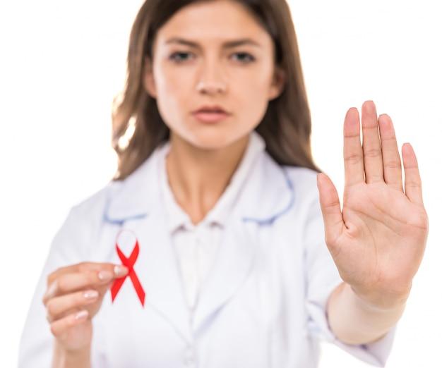 Doctor hermoso que sostiene la cinta roja como símbolo del sida.