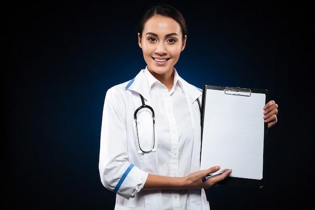 Doctor hermoso sonriente que muestra el tablero en blanco aislado sobre negro