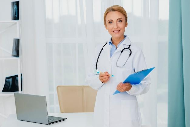 Doctor holding portapapeles mirando a cámara
