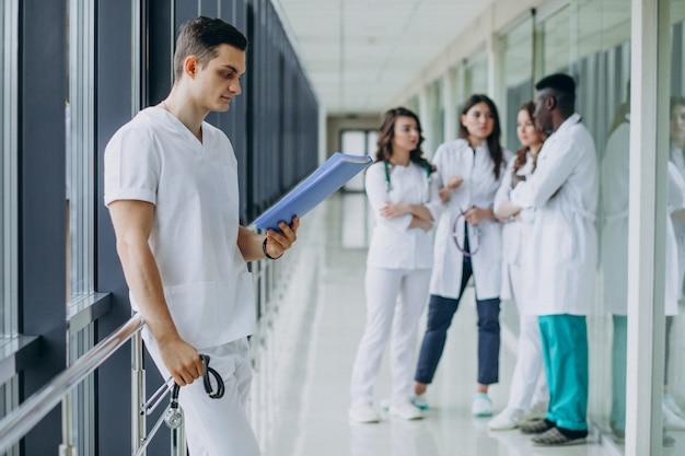 Doctor hombre con documentos de diagnóstico en el pasillo del hospital.