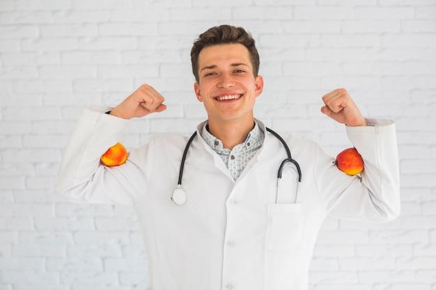 Doctor hombre flexionando sus manos sosteniendo manzanas rojas en su bíceps