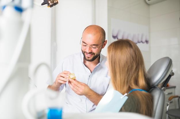 Doctor hombre hablando con paciente mostrando mandíbula dental