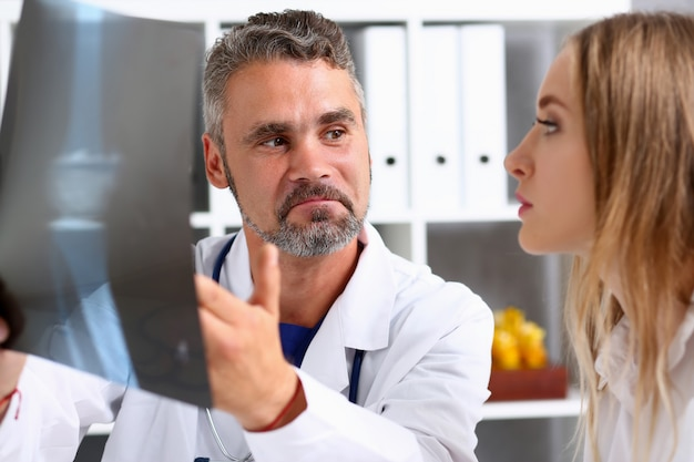 Doctor hombre maduro sostenga en el brazo y mire la fotografía de rayos
