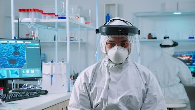 Doctor hombre mirando a la cámara sentado en un laboratorio equipado científicamente vestido con un traje de protección contra el coronavirus. examinar la evolución del virus utilizando herramientas químicas de alta tecnología para el desarrollo de vacunas.