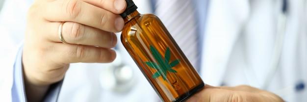 Doctor hombre sostenga la botella con aceite de marihuana