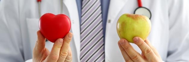 Doctor hombre sosteniendo corazón rojo y manzana closeup