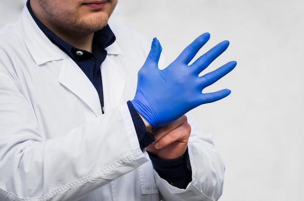 El doctor de los hombres que lleva los guantes quirúrgicos azules contra el fondo blanco