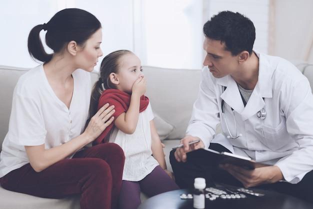 El doctor interroga a la niña y a su madre.
