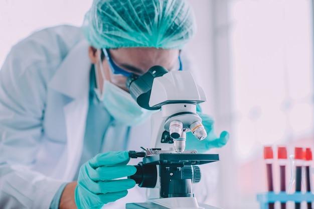 Doctor investigación vacuna corona virus, doctor analizando microscopio en laboratorio hospital