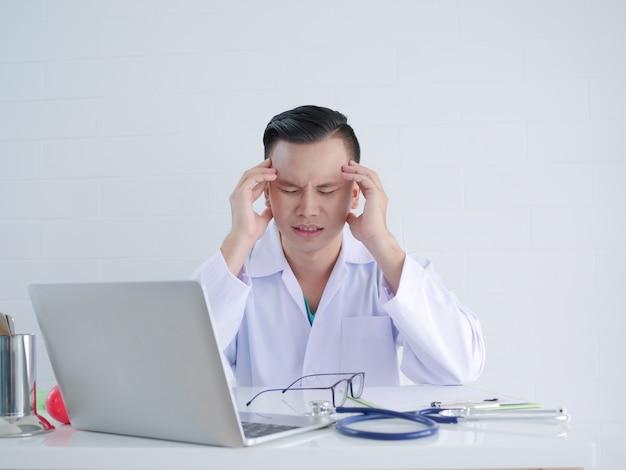 Doctor joven dolor de cabeza durante el trabajo.
