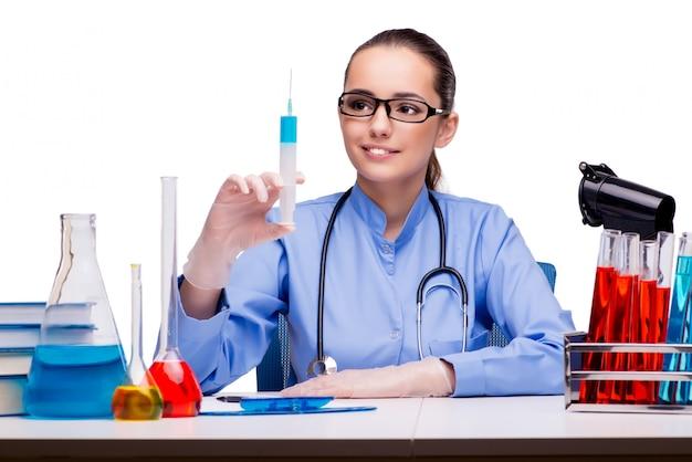Doctor joven con la jeringuilla aislada en blanco