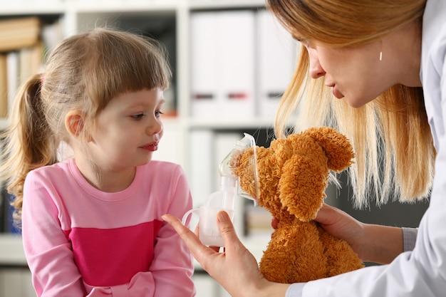 Doctor jugar con poco paciente dando inhalador para juguete
