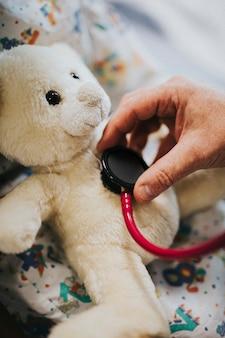 Doctor juguetonamente comprobando el latido del corazón de un oso de peluche