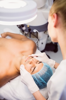 Doctor limpiando la cara del paciente con una esponja facial