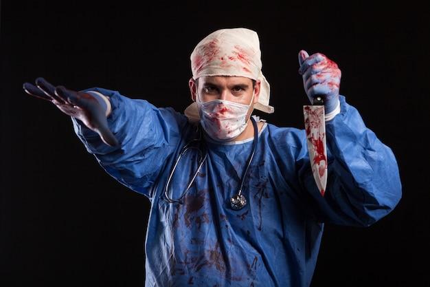 Doctor loco sosteniendo un cuchillo cubierto de sangre en estudio sobre fondo negro. médico maníaco con máscara sobre su rostro para halloween.