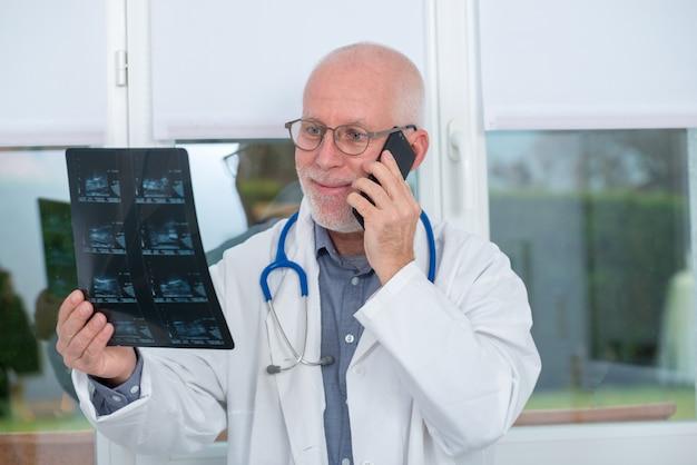 Doctor maduro mirando la imagen de rayos xy usando el teléfono
