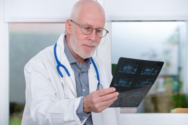 Doctor maduro mirando una radiografía en la oficina