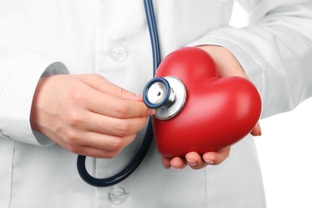 Doctor manos con estetoscopio y corazón rojo, primer plano