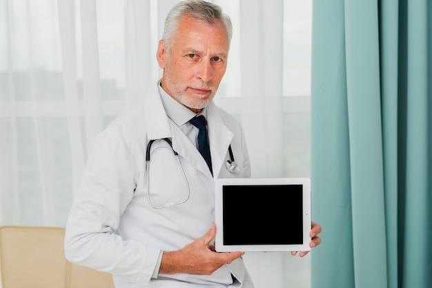 Doctor de maqueta que sostiene la tableta