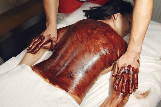 El doctor masajea a la mujer con un chocolate.
